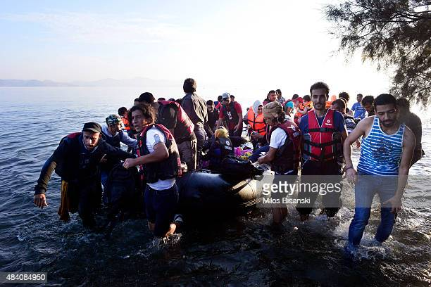 Syrian refugees arrive at a beach on the Greek island of Kos after crossing a part of the Aegean sea from Turkey to Greece in a dinghy on August 15...