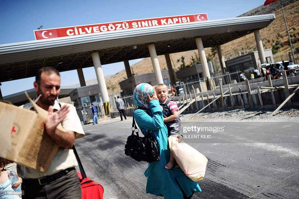 Syrian refugees arrive in Turkey at the Cilvegozu crossing gate of Reyhanli, in Hatay, on August 31, 2013. Syrian President Bashar al-Assad vowed on August 31, 2013 to defend Syria from attack as Washington and London laid out their case for punitive military strikes against Damascus over suspected poisonous gas attacks. Hundreds of people including children were reportedly killed when poisonous gas was unleashed on the outskirts of Damascus on August 21.