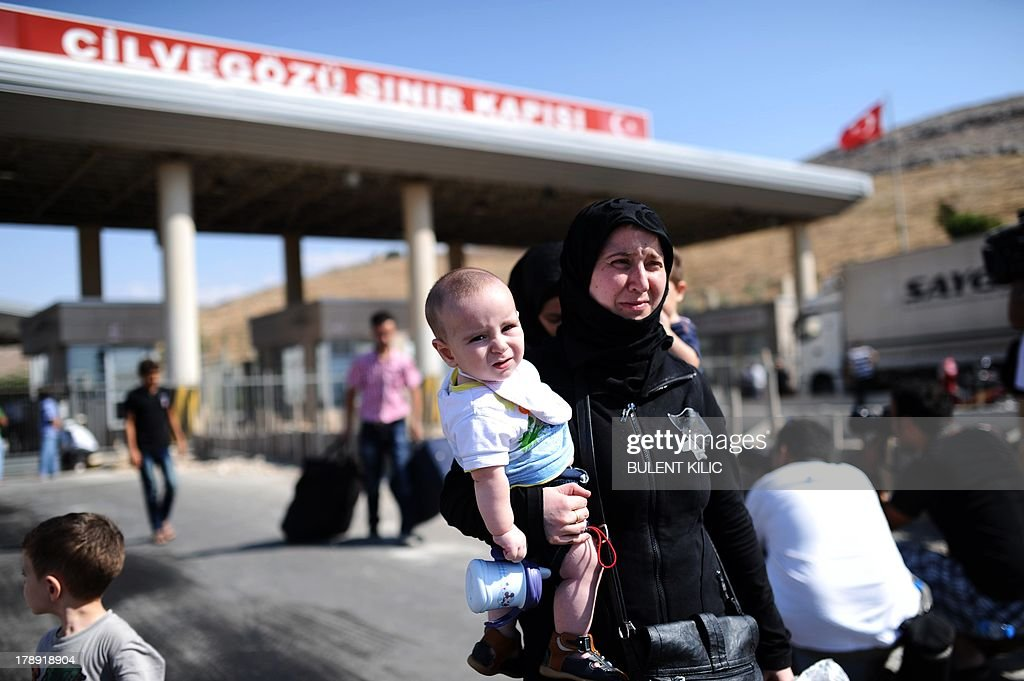 Syrian refugees arrive in Turkey at the Cilvegozu crossing gate of Reyhanli, in Hatay, on August 31, 2013. Syrian President Bashar al-Assad vowed on August 31, 2013 to defend Syria from attack as Washington and London laid out their case for punitive military strikes against Damascus over suspected poisonous gas attacks. Hundreds of people including children were reportedly killed when poisonous gas was unleashed on the outskirts of Damascus on August 21. AFP PHOTO / BULENT KILIC