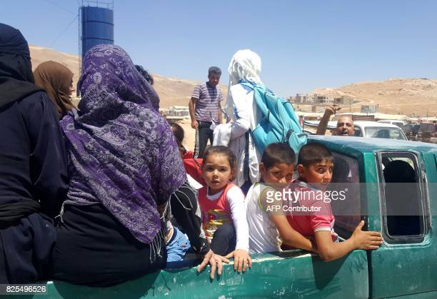 Syrian refugees arrive in Wadi Hamayyed on the outskirts of Lebanon's northeastern border town of Arsal to board buses bound for the northwestern...