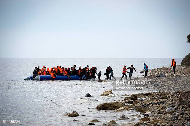 Syrian refugees arrive on an inflatable boat with other refugee after crossing the sea from Turkey to Lesbos some 5 kilometres south of the capital...
