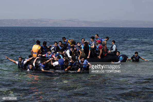 Syrian refugees arrive on the shores of the Greek island of Lesbos after crossing the Aegean Sea from Turkey on a inflatable dinghy on September 11...