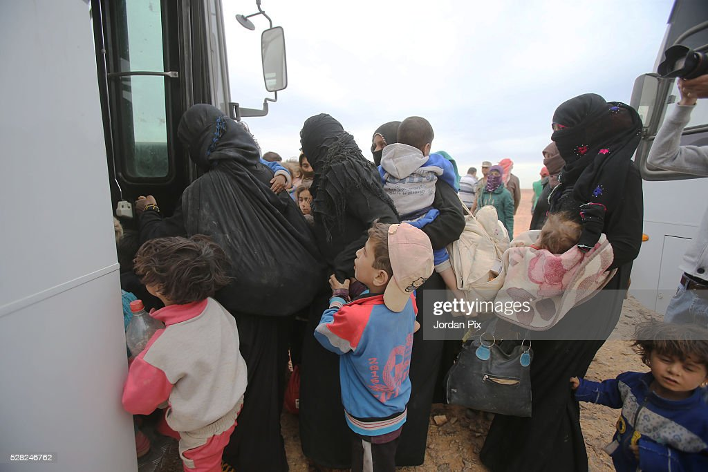 Syrian refugees board a bus at the Jordanian military crossing point of Hadalat at the border with Syria after a long walk through the Syrian desert on May 4, 2016 in Hadalat, Jordan. Coming from the cities of Raqaa, Deir Al-Zor and Hama, roughly 300 hundred refugees crossed into Jordan at Hadalat on Wednesday, while over 5000 refugees crossed in the last four days coming from Aleppo.
