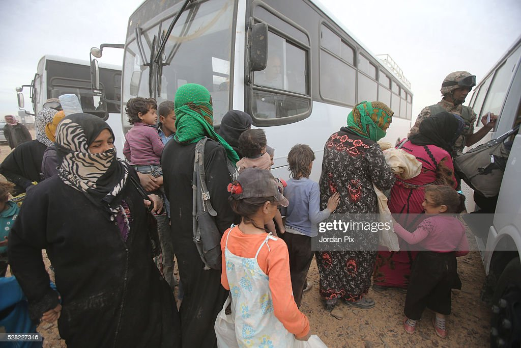 Syrian refugees board buses at the Jordanian military crossing point of Hadalat at the border with Syria after a long walk through the Syrian desert on May 4, 2016 in Hadalat, Jordan. Coming from the cities of Raqaa, Deir Al-Zor and Hama, roughly 300 hundred refugees crossed into Jordan at Hadalat on Wednesday, while over 5000 refugees crossed in the last four days coming from Aleppo.
