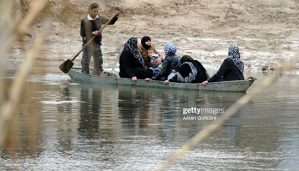 Syrian refugees board in a small paddle boat that will take them across the Orontes river to Turkey near the northern Syrian town of Darkush on January 30, 2013. Syria's opposition chief Moaz al-Khatib said he is ready for dialogue with officials of President Bashar al-Assad's regime, subject to conditions including that some 160,000 detainees are released. The United Nations says more than 60,000 people have been killed in Syria's 22-month conflict.