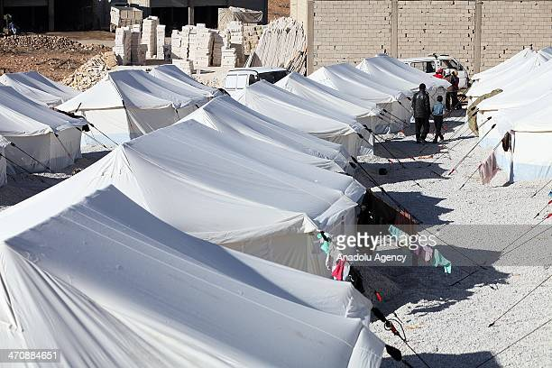 Syrian refugees build tents to house in a refugee camp in Lebanon's frontier town of Arsal on February 18 2014 in Beirut Lebanon Arsal refugee camp...
