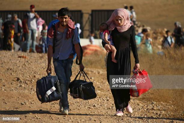 TOPSHOT Syrian refugees carry belongings as they return to Syria after crossing the Jordanian border near the town of Nasib in the southern province...
