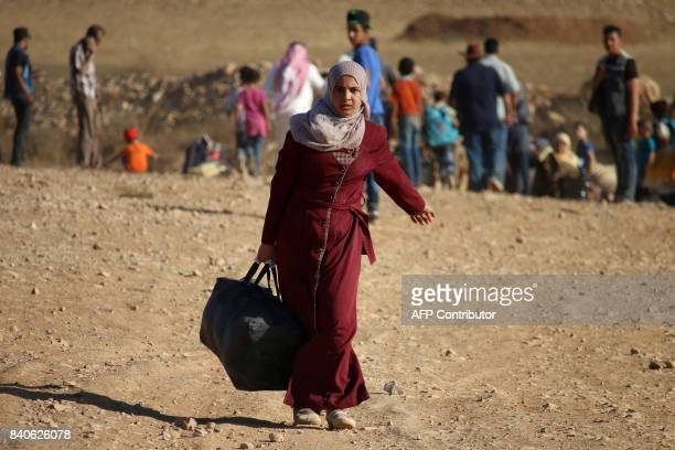 Syrian refugees carry belongings as they return to Syria after crossing the Jordanian border near the town of Nasib in the southern province of Daraa...