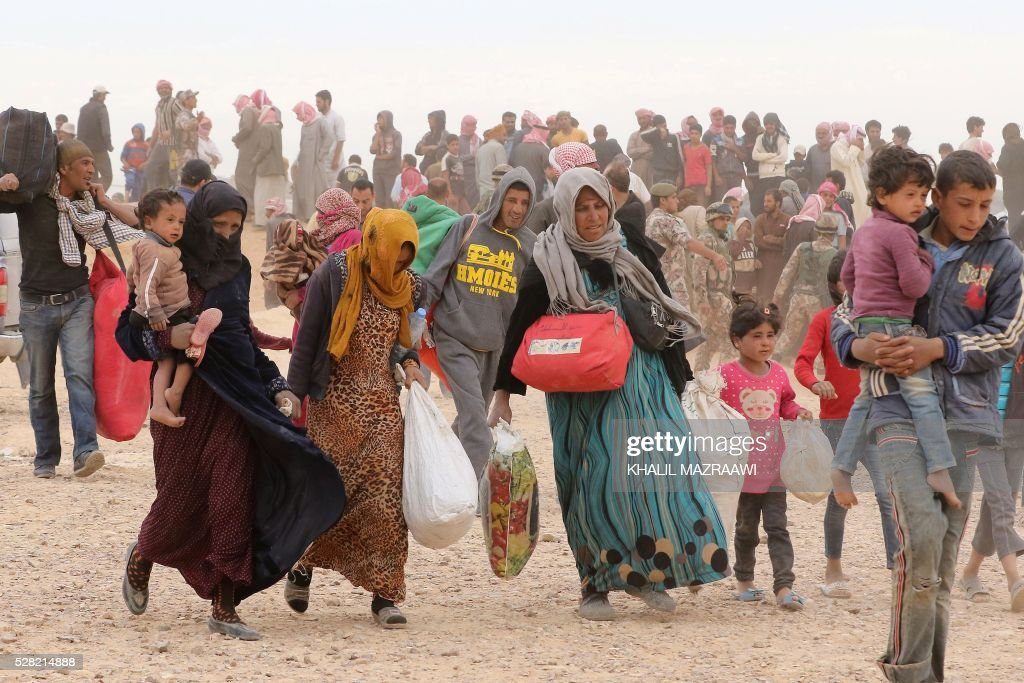 Syrian refugees carry their belongings as they wait to enter Jordanian side of the Hadalat border crossing, a military zone east of the capital Amman, after arriving from Syria on May 4, 2016. According to the Jordanian Commander of the Border Guards Brigadier Saber Al-Mahayreh, around 5000 Syrians fleeing from recent attacks on the northern Syrian city of Aleppo are trying to cross into Jordan in search of safety and most are exhausted and desperately in need of help and medical treatment. MAZRAAWI