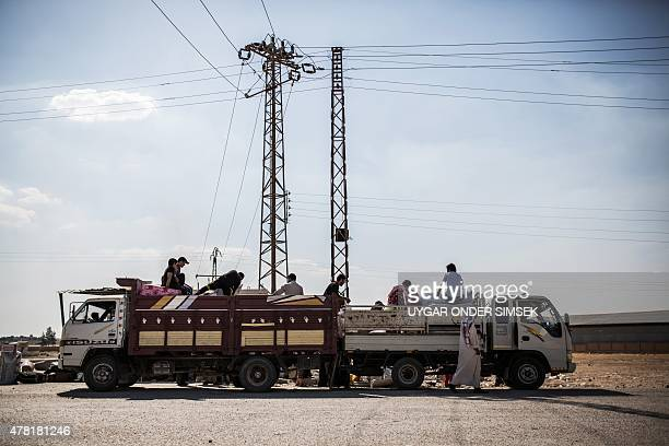 Syrian refugees carrying their belongings cross the SyriaTurkey border on June 22 as they return to the northern Syrian town of Tal Abyad in Syria's...