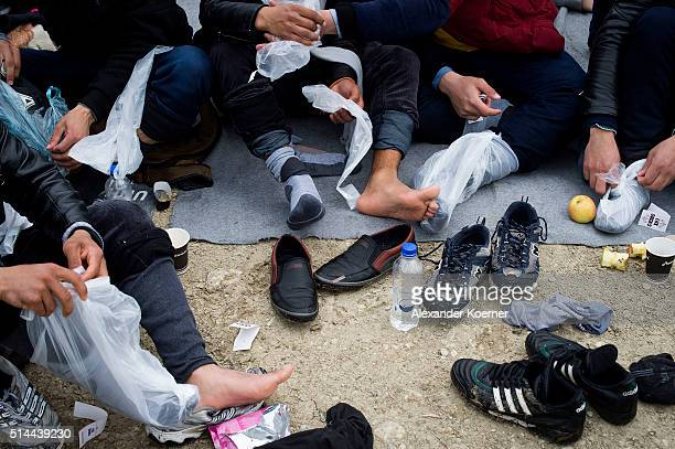 Syrian refugees change their socks after arriving on the beach crossing the sea from Turkey to Lesbos some 5 kilometres south of the capital of the...