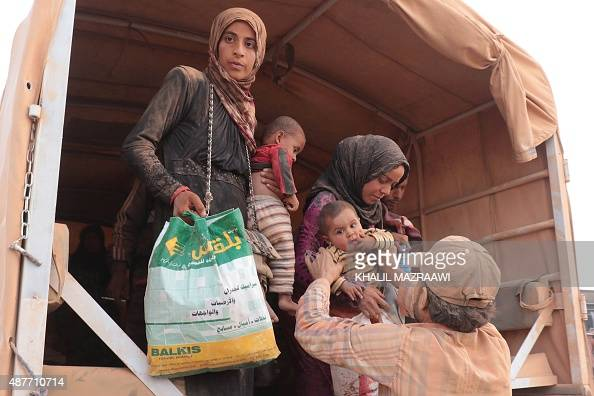 Syrian refugees covered with dust arrive in the eastern town of Ruwaished where they were welcomed and checked by the Jordanian authorities after a...