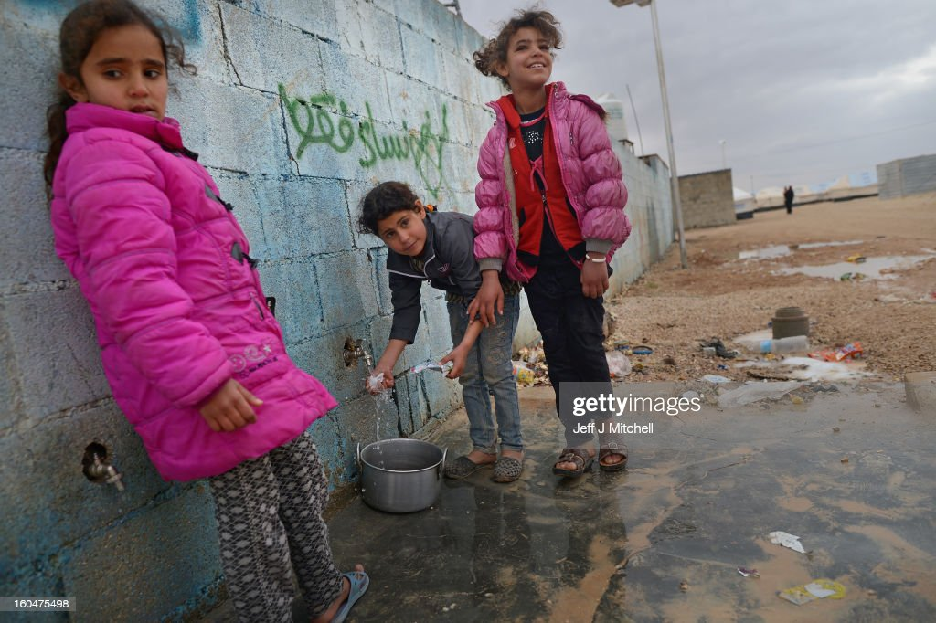 ZA'ATARI, JORDAN - FEBRUARY 01: Syrian refugees fetch water in the Za'atari refugee camp on February 1, 2013 in Za'atari, Jordan. Record numbers of refugees are fleeing the violence and bombings in Syria to cross the borders to safety in northern Jordan and overwhelming the Za'atari camp. The Jordanian government are appealing for help with the influx of refugees as they struggle to cope with the sheer numbers arriving in the country.