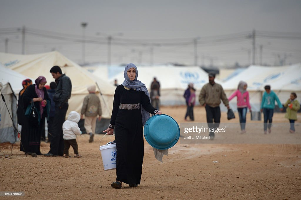 Syrian refugees fetch water in the Za'atari refugee camp on February 1, 2013 in Za'atari, Jordan. Record numbers of refugees are fleeing the violence and bombings in Syria to cross the borders to safety in northern Jordan and overwhelming the Za'atari camp. The Jordanian government are appealing for help with the influx of refugees as they struggle to cope with the sheer numbers arriving in the country.