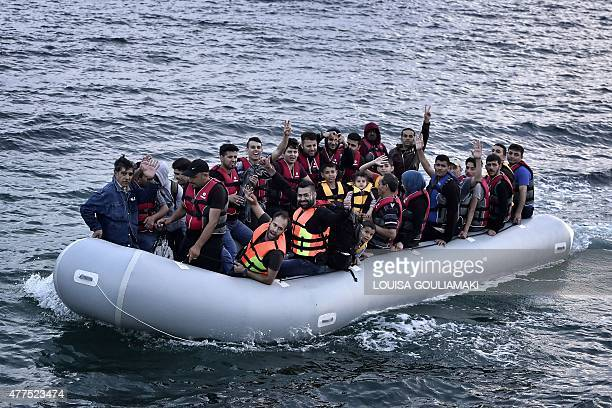 Syrian refugees flash the victory sign as they sit aboard a dinghy carrying heading to the island of Lesbos early on June 18 2015 Some 48000 migrants...
