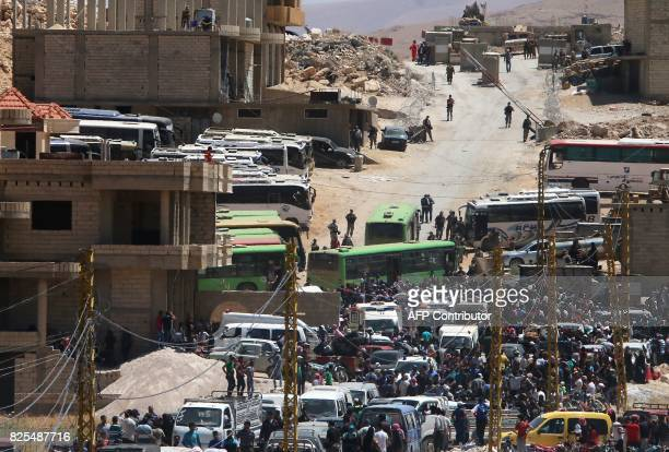 Syrian refugees gather around buses bound for the northwestern Syrian town of Idlib as they wait to board in Wadi Hamayyed on the outskirts of...