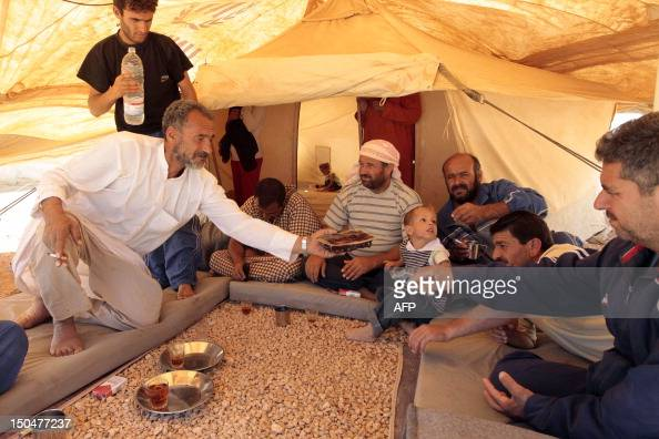 Syrian refugees gather in a tent at the Zaatari refugee camp close to the northern Jordanian city of Mafraq near the border with Syria on the first...