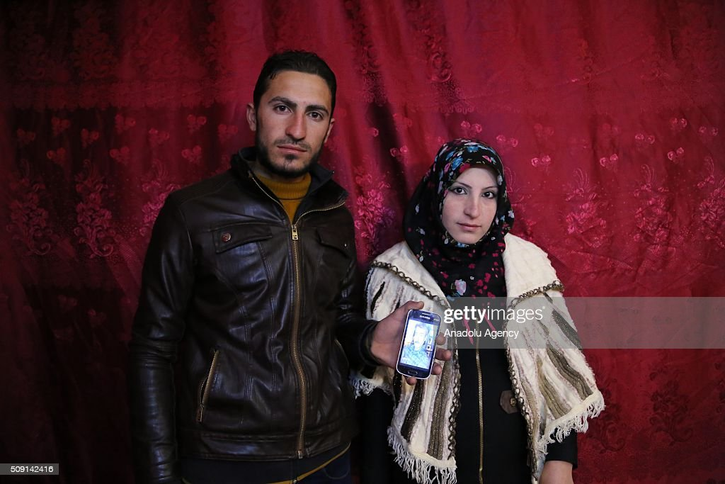 Syrian refugees Housem Suleyman (L) and his wife Busra Omar (R), fled 4,5 years ago from Syria's Hama due to ongoing civil-war, pose with Housem's father's picture at their house in Turkey's Syrian border city Hatay's Reyhanli District on February 08, 2016. Housem had lost his father due to a Assad Regime's barrel bomb attack. Turkey spent US$ 8 Billion and hosts approximately 2 million refugees.