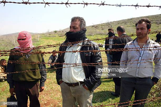 Syrian refugees look through barbed wire from the Syrian side near Reyhanli Hatay province at the border between Syria and Turkey on March 27 2012...