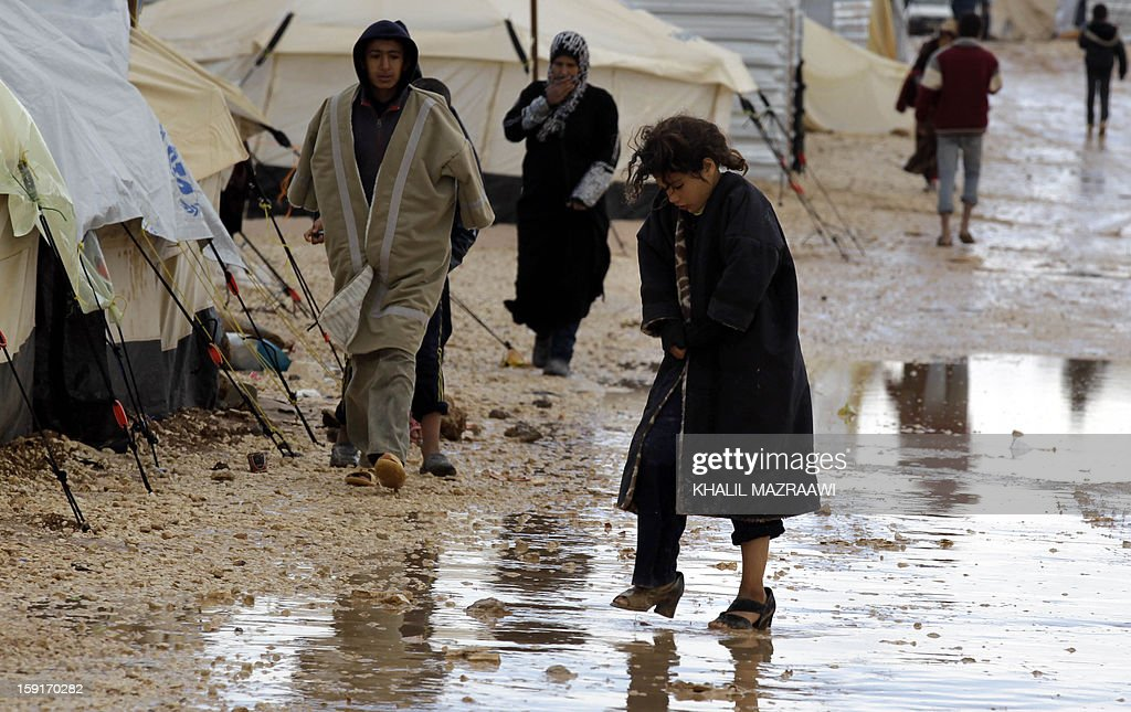 Syrian refugees make their way through muddy ground at the Zaatari refugee camp, near the Syrian border with Jordan in Mafraq on January 9, 2013. Thousands of Syrian refugees are appealing for help after three days of rain and winter storm left them battling mud, water, freezing temperatures and increasing misery.