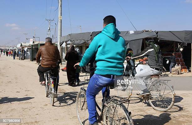Syrian refugees men ride bikes in a street on February 2 2016 in the Zaatari camp in northeast Jordan King Abdullah of Jordan has said the huge...
