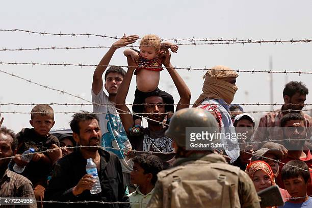 Syrian refugees passing on the Syrian side of the border crossing Akcakale on June 15 2015 in Sanliurfa province southeastern Turkey Thousands of...