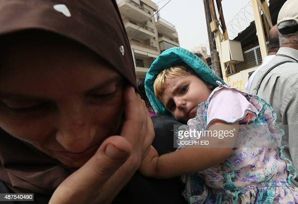 Syrian refugees queue to apply for immigration outside the German Embassy on the northern outskirts of Beirut on September 10 2015 Lebanon with a...