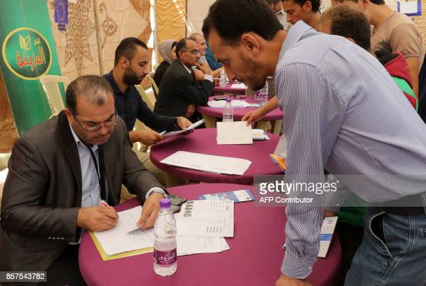 Syrian refugees queue to register their names at the Zaatari office for employment on October 4 2017 at the Zaatari refugee camp 80 kilometers north...