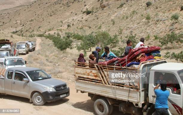 Syrian refugees ride vehicles in the Lebanese eastern border town of Arsal as they head towards the Syrian region of Qalamoun on July 12 2017 as part...