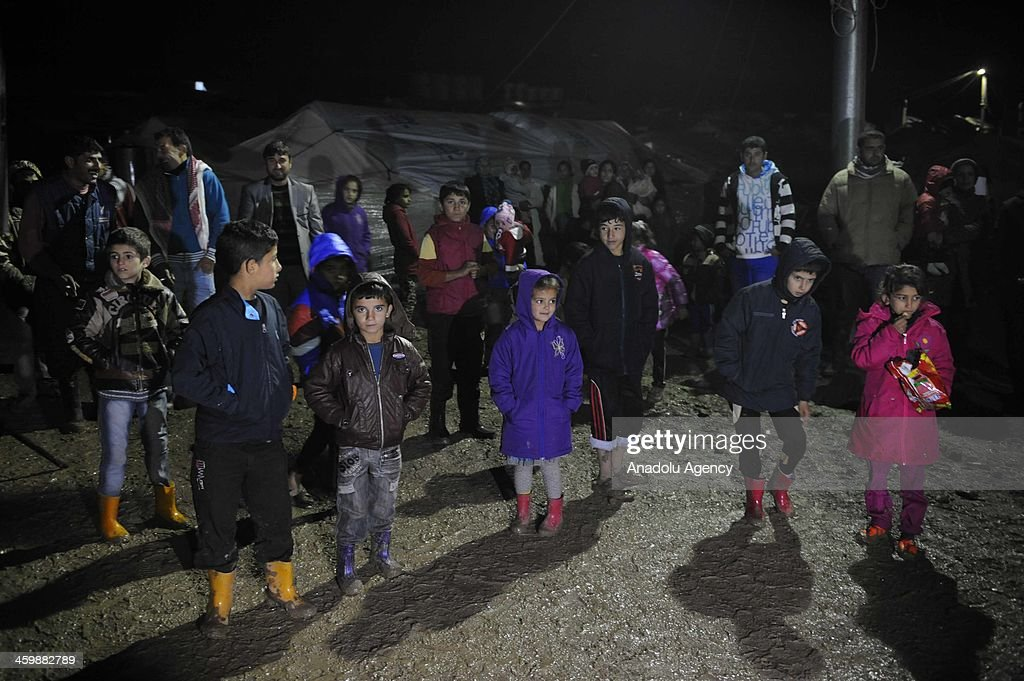 Syrian refugees sheltering at Iraqi Kurdish regional administration refugee camp in Erbil, Iraq greet arrival of the New Year with sorrow at their tents on January 1, 2014.