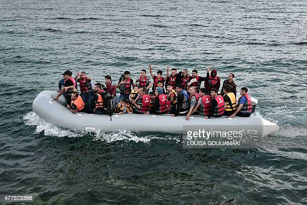 Syrian refugees sit aboard a dinghy carrying heading to the island of Lesbos early on June 18 2015 Some 48000 migrants and refugees have landed on...