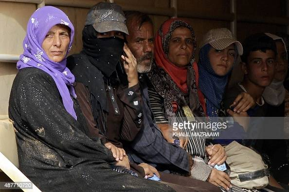 Syrian refugees sit in the back of a Jordanian army truck as they leave the alRoqban makeshift camp on the border with Syria for the eastern town of...