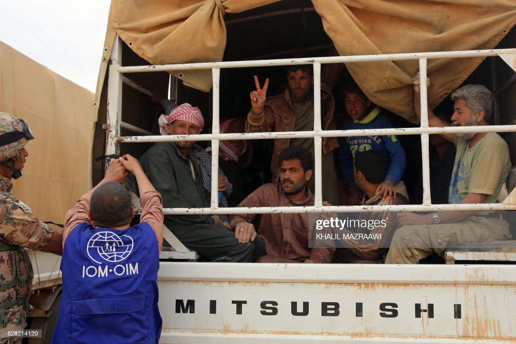 Syrian refugees sit in the back of a vehicle as they wait to cross to the Jordanian side of the Hadalat border crossing, a military zone east of the capital Amman, after arriving from Syria on May 4, 2016. According to the Jordanian Commander of the Border Guards Brigadier Saber Al-Mahayreh, around 5000 Syrians fleeing from recent attacks on the northern Syrian city of Aleppo are trying to cross into Jordan in search of safety, most of whom are exhausted and desperately in need of help and medical treatment. MAZRAAWI