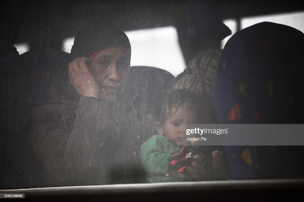Syrian refugees sit on a bus that will take them to a camp at the Jordanian military crossing point of Hadalat at the border with Syria after a long walk through the Syrian desert on May 4, 2016 in Hadalat, Jordan. Coming from the cities of Raqaa, Deir Al-Zor and Hama, roughly 300 hundred refugees crossed into Jordan at Hadalat on Wednesday, while over 5000 refugees crossed in the last four days coming from Aleppo.
