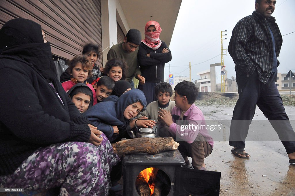 Syrian refugees sits around a wood burning oven in Kfarkahel village, in the Koura district close to the northern city of Tripoli on January 9, 2013. As stormy weather sparked widespread flooding, prompting chaos on the roads and a nationwide school closure. The number of Syrian refugees in Lebanon is already totalling 156,000, according to UN figures, and 200,000 according to the Lebanese government estimates. AFP PHOTO/Ibrahim Chalhoub