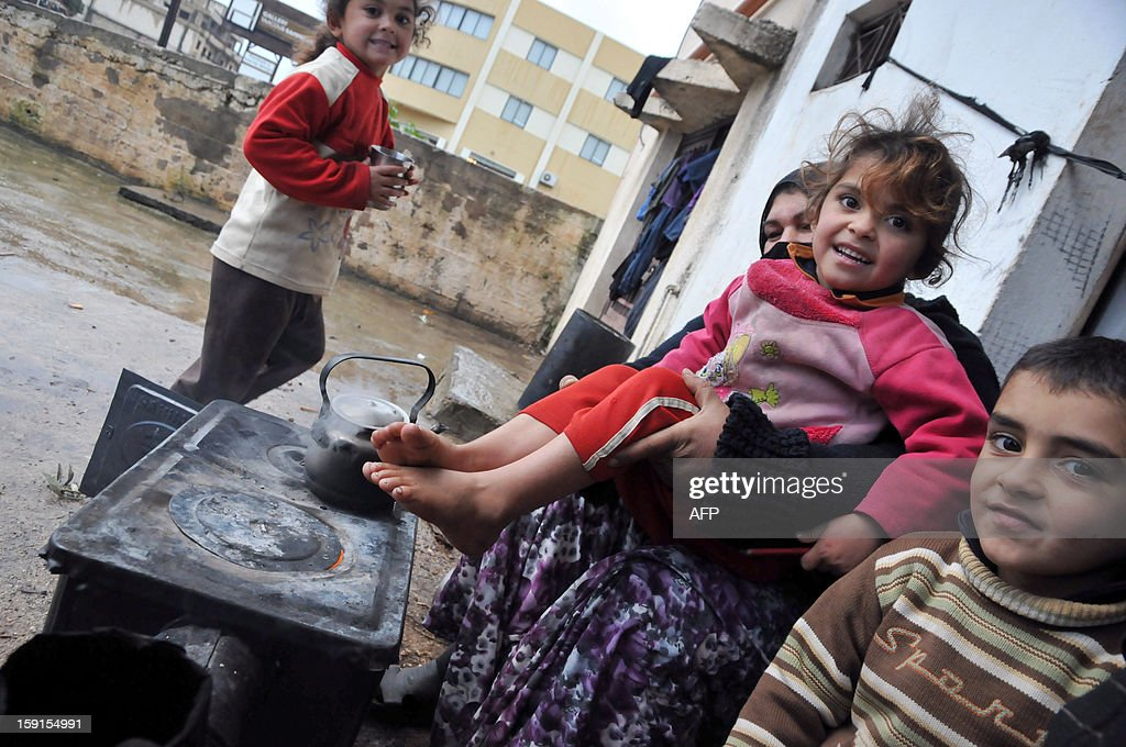 Syrian refugees sits around a wood burning oven in Kfarkahel village, in the Koura district close to the northern city of Tripoli on January 9, 2013, as stormy weather sparked widespread flooding, prompting chaos on the roads and a nationwide school closure. The number of Syrian refugees in Lebanon is already totalling 156,000, according to UN figures, and 200,000 according to the Lebanese government estimates. AFP PHOTO/Ibrahim Chalhoub