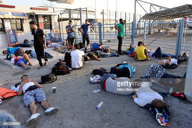 Syrian refugees sleepsin front of closed port gates while waiting to board the passenger ship 'Eleftherios Venizelos' at Kos's main port on August 16...
