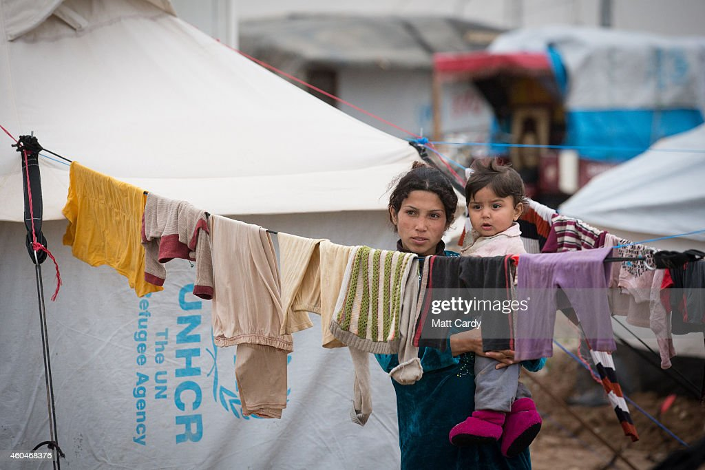 Syrian refugees stand besides the door of their home at the Qushtapa Refugee Camp on December 14 2014 in Erbil Iraq Although the autonomous Kurdistan...