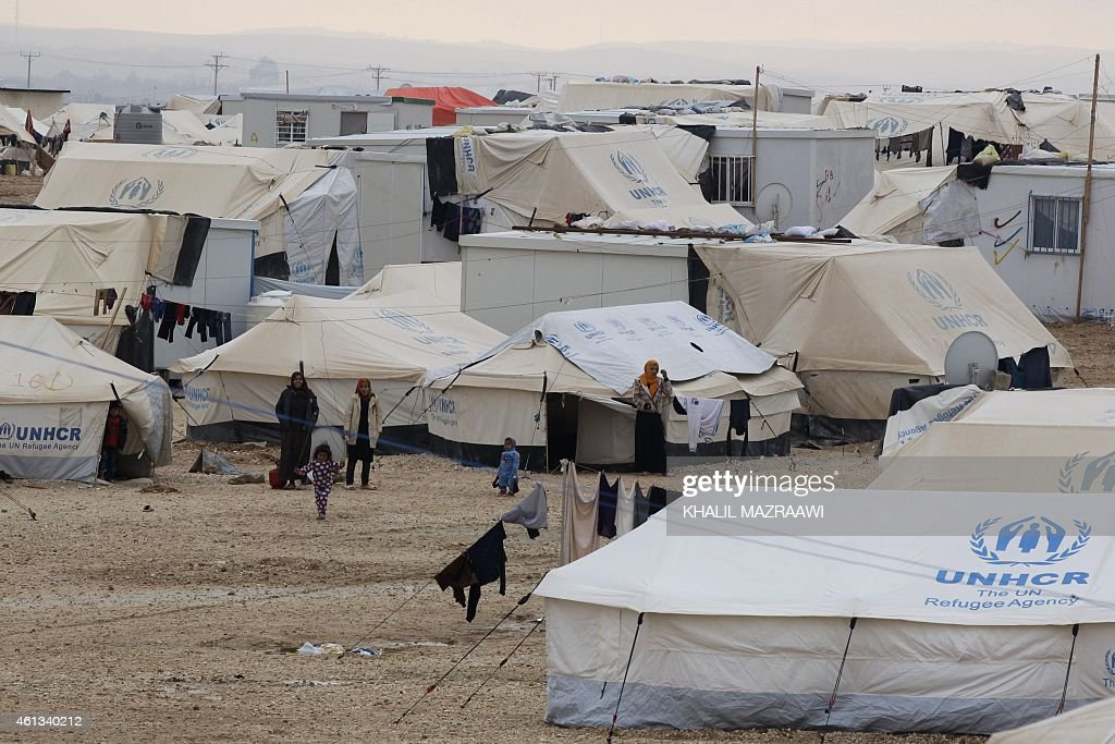 Syrian refugees stand next to tents at the UNrun Zaatari refugee camp north east of the Jordanian capital Amman on January 11 as a fierce winter...