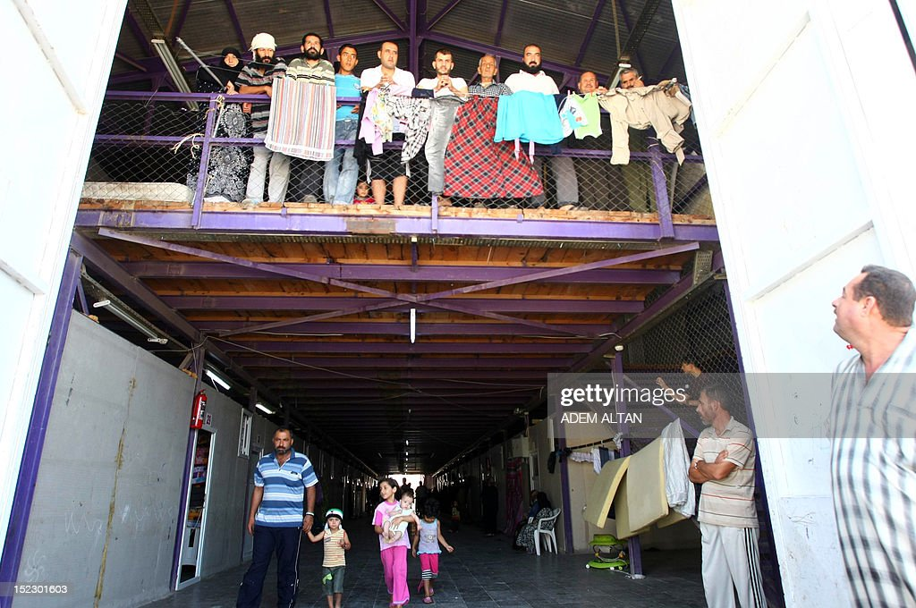 Syrian refugees stand on a balcony as they wait for the International peace envoy for Syria to arrive in the Altinozu camp in Hatay city, located on the border with their violence-racked homeland, on September 18, 2012. The Altinozu camp is one of the first refugee camps set up by Turkey soon after the unrest erupted in Syria mid-March 2011, which has already killed 20,000 according to UN figures and forced 250,000 to flee into neighbouring countries.