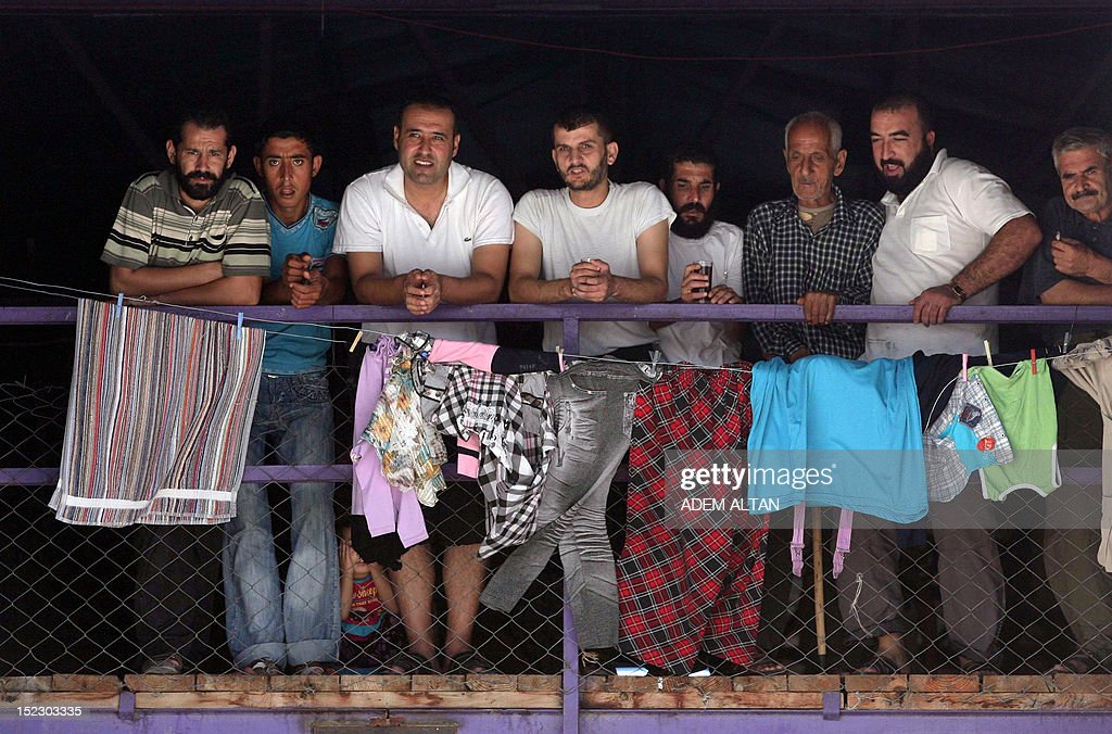 Syrian refugees stand on a balcony as watch the International peace envoy for Syria visiting the Altinozu camp in Hatay city, located on the border with their violence-racked homeland, on September 18, 2012. The international peace envoy for Syria Lakhdar Brahimi on September 18 met Syrians staying at a Turkish refugee camp in his first encounter since taking over the mission from his frustrated predecessor. The Altinozu camp is one of the first refugee camps set up by Turkey soon after the unrest erupted in Syria mid-March 2011, which has already killed 20,000 according to UN figures and forced 250,000 to flee into neighbouring countries.