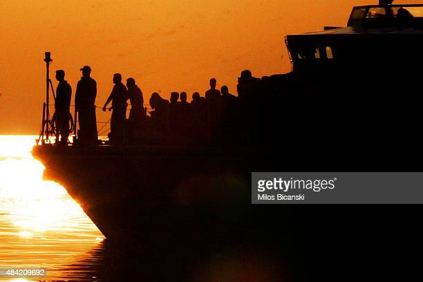 Syrian refugees stand on the Frontex patrol boat while they are escorted board the ship 'Eleftherios Venizelos' at Kos's main port on August 16 2015...