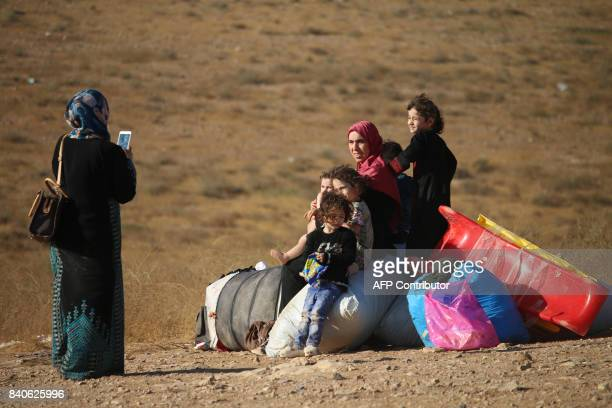 Syrian refugees take a picture on the side of the road as they return to Syria after crossing the Jordanian border near the town of Nasib in the...