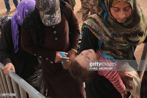 Syrian refugees wait at the alRoqban makeshift camp on the border with Syria before being driven by the Jordanian army to the eastern town of...
