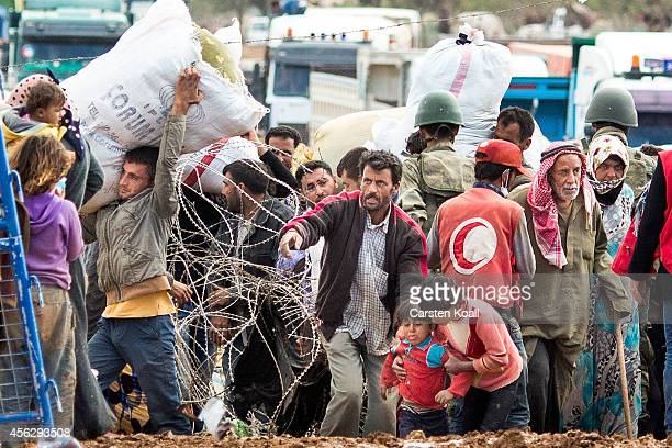 Syrian refugees wait behind barbed wire at a border crossing point after crossing from Syria into Turkey in Yumurtalik September 28 2014 south of...