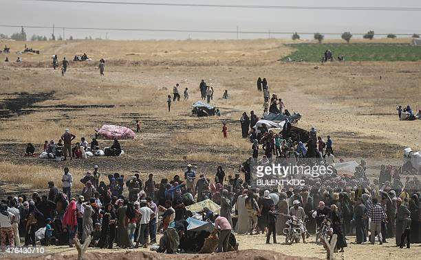 Syrian refugees wait between Syria and Turkish border as Turkish soldiers block them to pass Turkish side on June 9 at Akcakale in Sanliurfa province...
