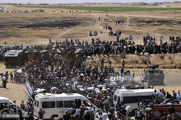 Syrian refugees wait for transportation after crossing into Turkey from the Syrian town of Tal Abyad near Akcakale in Sanliurfa province on June 10...