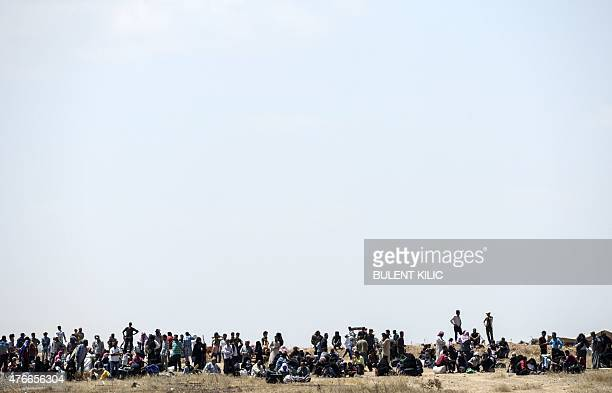 Syrian refugees wait near the Turkish border in Akcakale in the Sanliurfa province not far from the Syrian town of Tal Abyad on June 11 2015 More...