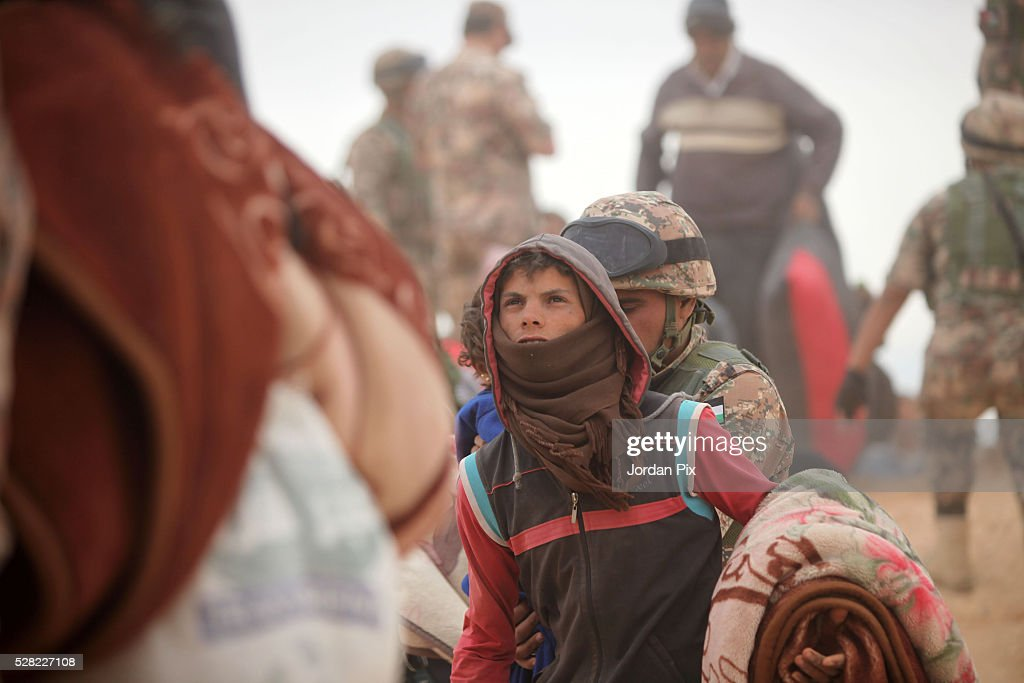 Syrian refugees wait to board buses at the Jordanian military crossing point of Hadalat at the border with Syria after a long walk through the Syrian desert on May 4, 2016 in Hadalat, Jordan. Coming from the cities of Raqaa, Deir Al-Zor and Hama, roughly 300 hundred refugees crossed into Jordan at Hadalat on Wednesday, while over 5000 refugees crossed in the last four days coming from Aleppo.