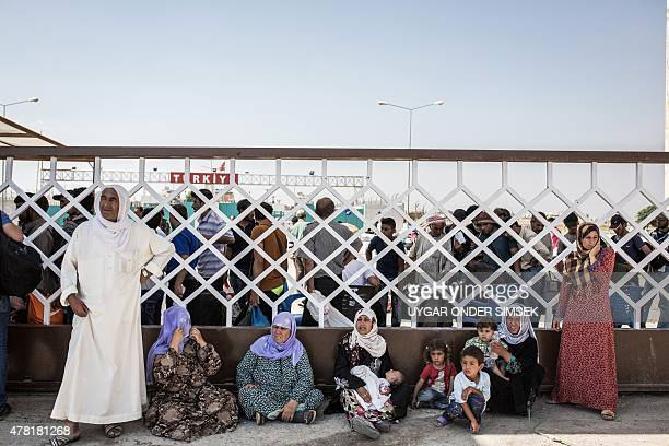 Syrian refugees wait to cross the SyriaTurkey border crossing on June 22 as they return to the northern Syrian town of Tal Abyad on the border with...